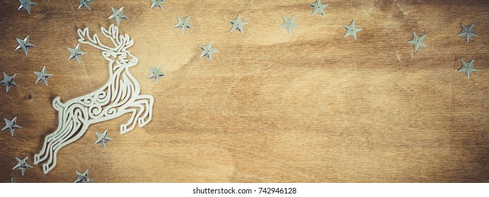 Christmas Background for Holiday Card in Rustic Style. Xmas Decorative Deer on Wooden Board. Copy Space for Your Text. Toned image.