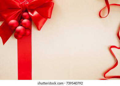 Christmas background for holiday themes. Red silk bow, ribbon and velvet ribbon with Christmas balls. Copy space for your holiday messages.