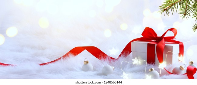 Christmas background with holidays gift box and Christmas decoration on red background