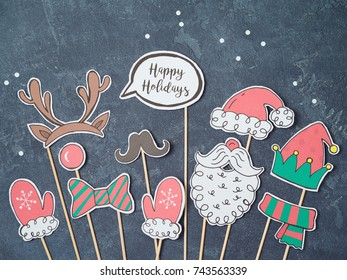 Christmas background with homemade photo booth props. Santa beard, hat, reindeer and elf. Party celebration concept