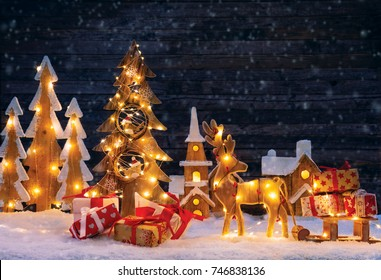 Christmas background with illuminated wooden village, moose and Christmas tree. Dark wooden background with free space for text. Celebration of Christmas