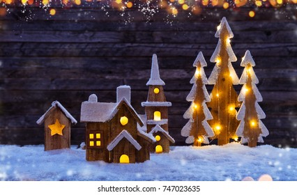 Christmas background with illuminated wooden village and trees. Dark wooden background with free space for text. Celebration of christmas