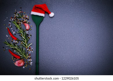 Christmas background with Kitchen green silicone spoon in Santa Claus red hat, pepper, peperoni, salt, rosemary,  garlic on dark background, top view. Herbs and spices Christmas top table.