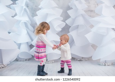 christmas background little girls sisters drinking milk with white christmas trees background
