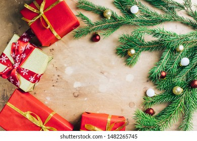 Christmas background made with evergreen tree branches, red, white and gold decorations on a beige stone background. Flat lay, copy space for your text. Nature New Year concept.