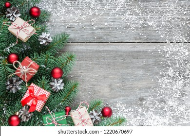 christmas background made of fir branches, decorations, gift boxes and pine cones on rustic wooden table covered with snow. Flat lay. top view with copy space