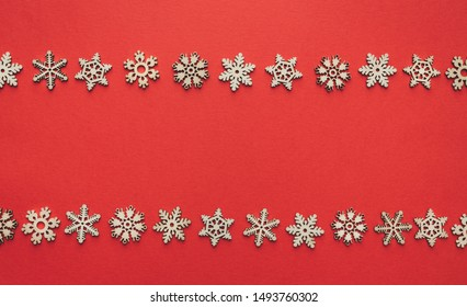 Christmas background made of wooden snowflakes against red. Copy space. Flat lay. View from above.