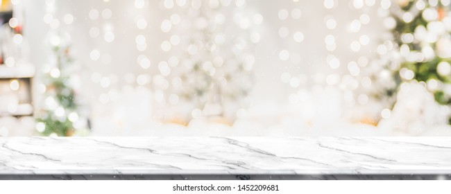 Christmas background of marble table top with abstract warm living room decor with christmas tree string light blur bokeh with snow,Holiday backdrop, panoramic Mock up banner for display of product