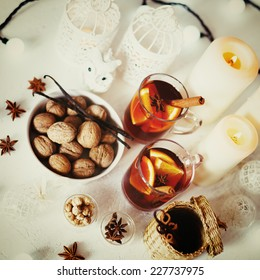 Christmas background with mulled wine, walnuts, candles and white decorations. Shallow dof, selective focus. Instagram vintage colors.