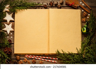 Christmas background - old blank open book with decorations around on vintage planked wood table from above. Layout with free text space.