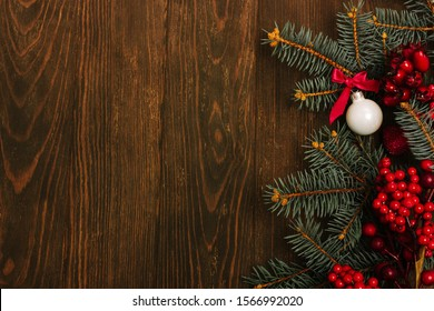 Christmas background on a dark wooden table. Composition with fir branches, red berries, balls, stars. Flat lay