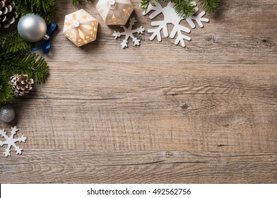 Christmas background on wooden table with copyspace. Top view of xmas tree with pine cone and snowflake. Christmas fir branch with silver balls.