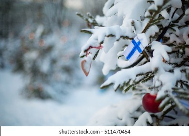Christmas background outdoor. Christmas tree covered with snow and decorations and a flag of Finland. Finnish flag closeup. Winter