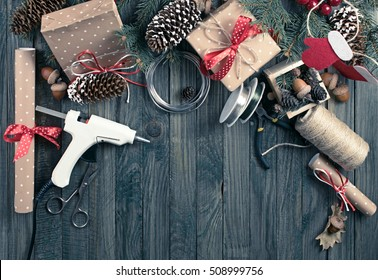 Christmas background. Packed gifts and scrolls, spruce branches and tools on shabby wooden table. Workplace for preparing handmade new year decorations. Winter holidays concept. Top view.