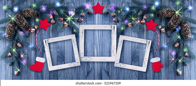 Christmas background with photo frame, illumination, glowing stars, spruce branches, pine cones, acorns. Winter holidays concept.