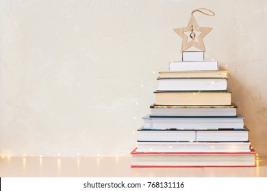 Christmas background with a pile of books and a wooden star