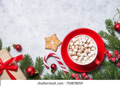 Christmas background. Christmas present box, cup of chocolate with marshmallow and decorations on gray stone background. Top view with copy space.