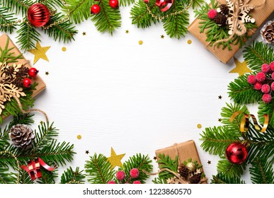Christmas background. Christmas presents in boxes and decorating elements on white wooden table. Flat lay with copy space.