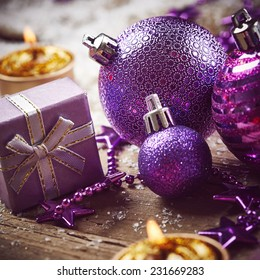 Christmas background with purple balls, golden candles and snow