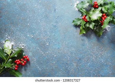 Christmas background with real holly leaves and red berries on a blue stone background covered in snow with copy space.