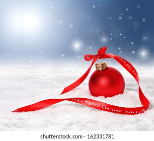 Christmas background with red bauble and merry christmas ribbon on snow with snowflakes falling from a blue sky