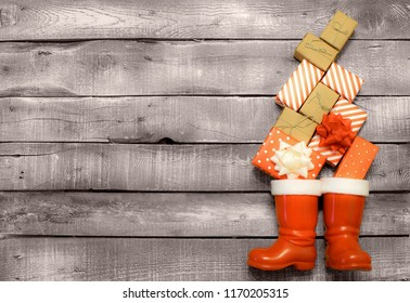 Christmas background - red and brown gifts fall down in Santas or Saint Nicholas boots on grey rustic wooden background