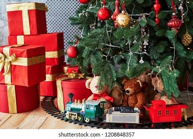 Christmas background with red gift boxes decorated with golden ribbon on floor and child toys under Christmas tree, copy space. Winter holidays concept