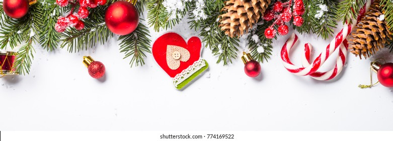 Christmas background. Red and gold christmas decorations with snow fir tree branch on white background isolated. Long banner format.