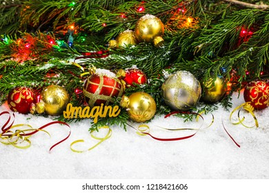 Christmas background with red and gold ornaments and ribbon, colorful string of lights, the word Imagine, and green Christmas tree garland border in snow; holiday background with white copy space