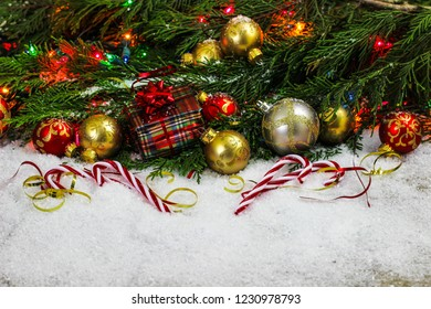 Christmas background with red and gold ornaments, candy canes, present, ribbon, colorful string of lights and green Christmas tree garland border in snow; holiday background with white copy space