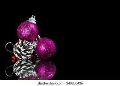 Christmas background with a red ornament and  brown pine cone on a black background