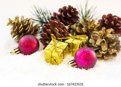 Christmas background with a red ornament, golden gift box and fir-cone in snow