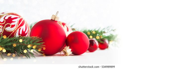 Christmas background with red christmas ornaments on white background with xmas tree, twinkle lights. Merry christmas greeting card, banner. Winter holiday xmas theme. Happy New Year. Space for text.