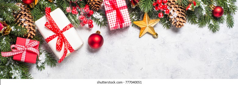 Christmas background. Red christmas present box, fir tree branch and decorations on gray stone table. Long banner format.