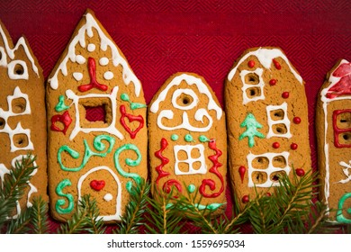 Christmas background. Red table cloth with town of cute gingerbread houses decorated with icing, Christmas lights, glitter and fir tree branches. Holiday mood.