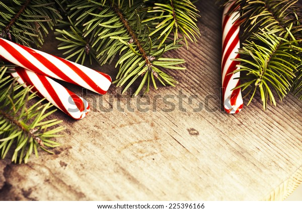 Christmas background with a red and white candie canes, fir branches with blank paper on wooden planks, wooden table background, New year theme