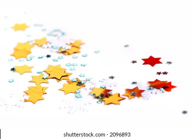 Christmas background of scattered glittering confetti on white