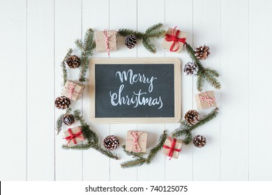 Christmas background with signboard and inscription, spruce, gift box and scroll on wooden boards.