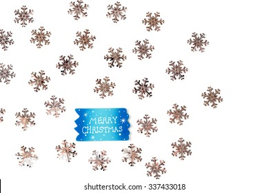 """Christmas Background with Silver Little Snowflakes and Sign with """"Merry Christmas"""" Text over White."""
