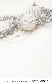 Christmas background with silver tinsel and white Christmas balls