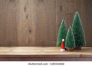 Christmas background with small pine trees and Santa hat on wooden table
