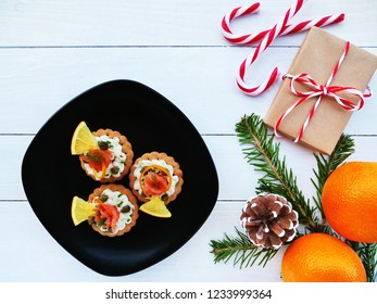 Christmas background with smoked salmon canapes on crackers over black plate, gift, candy cane, oranges and fir branches