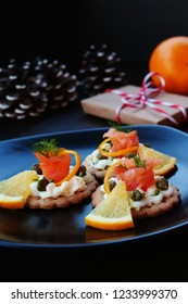 Christmas background with smoked salmon canapes and capers on crackers over black plate, gift, oranges and fir branches