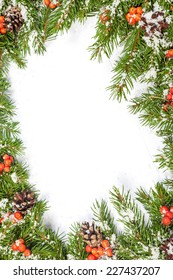 Christmas background with snow, cones and holly berry isolated on white