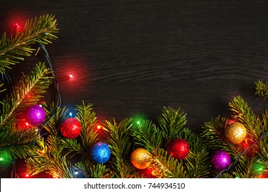 Christmas background with snow, fir tree branches, colorful xmas decorations and garland on dark wooden board. With copyspace in center