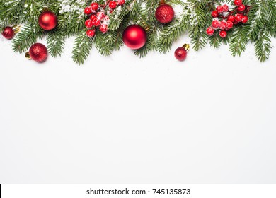 Christmas background. Snow Fir tree branch, red balls and berries on white background isolated. Top view with copy space.