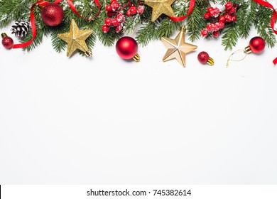 Christmas background. Snow Fir tree branch, gold star, red balls and berries on white background isolated. Top view with copy space.