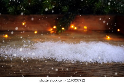 Christmas background, snow, lights, fir branches on wood with snow flakes