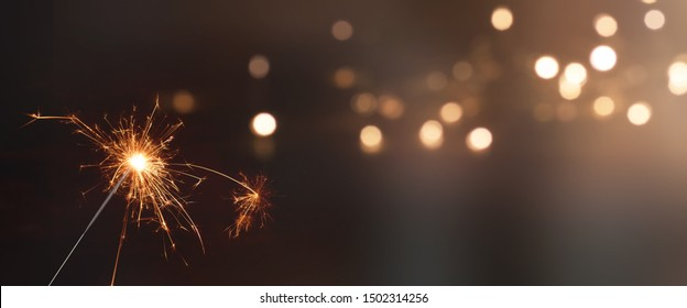 Christmas background with sparkler and festive golden bokeh