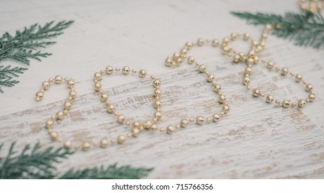 Christmas background with sprigs of arborvitae and gold Christmas beads, which form 2018 on white wooden background
